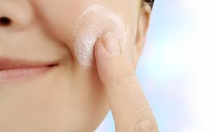 caucasian smiling woman applies moisturizer onto face